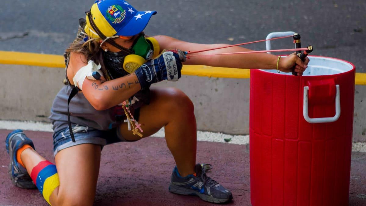 Mielenosoittaja tähtää ritsalla poliiseja Caracasissa, Venezuelassa 12.4.2014