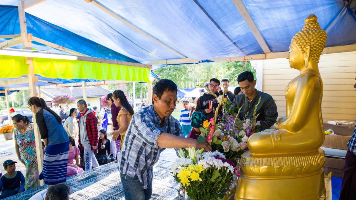 Ihmiset tuovat kukkia buddhan patsaalle.