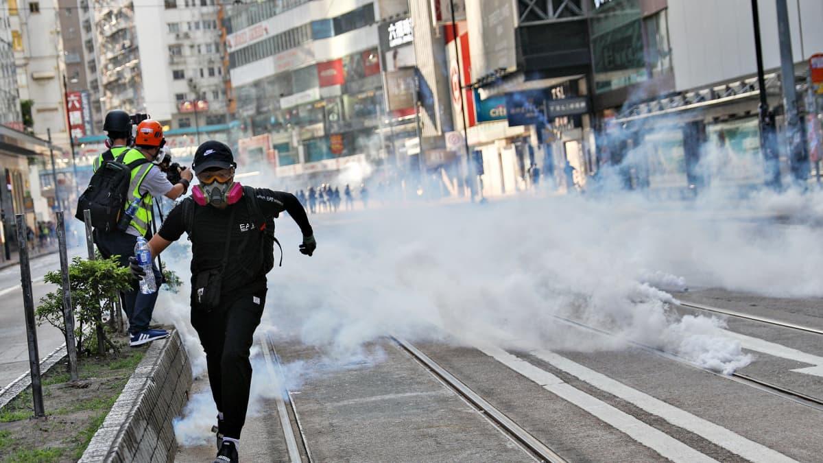 Mies juoksee kohti kuvaajaa, kun poliisit ovat ampuneet kyynelkaasupanoksia kadulle.