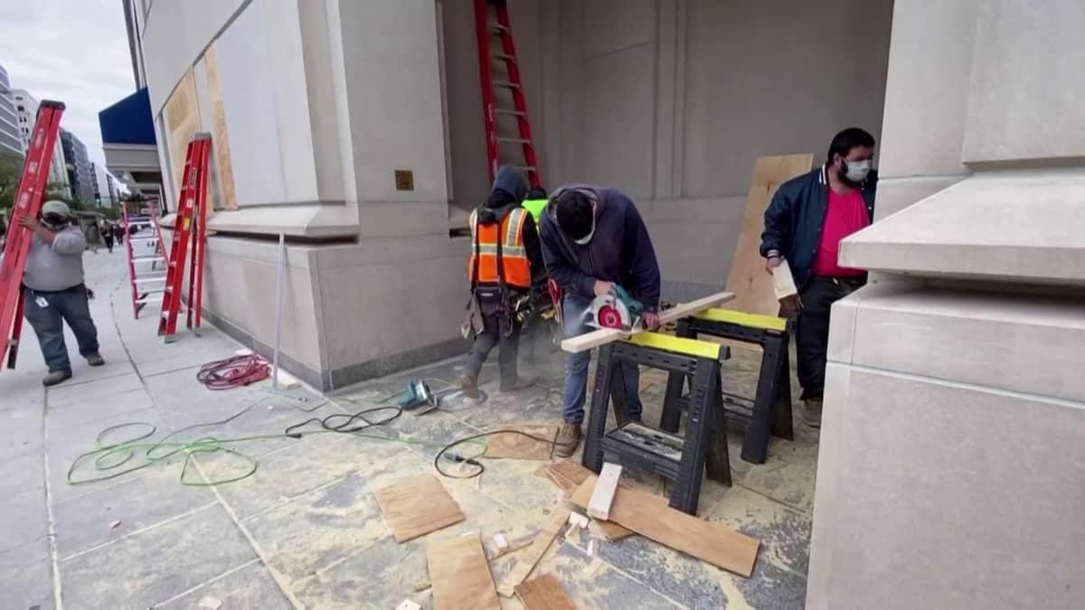 Miehiä töissä valmistamassa vanerisuojia ikkunoihin.