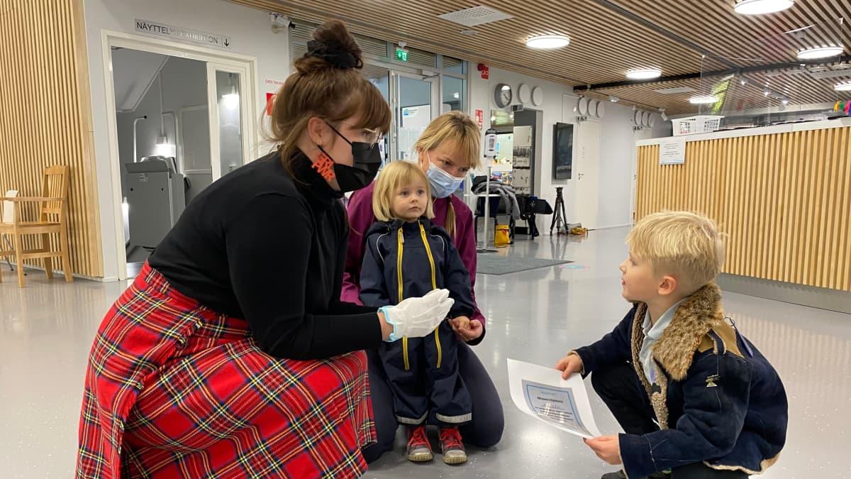 Lahden Hiihtomuseon amanuenssi Laura Häkkinen tutkii kyykyssä Ahti Valolan löytämää kiveä tämän kanssa. Valolan äiti ja sisko seisovat takana.