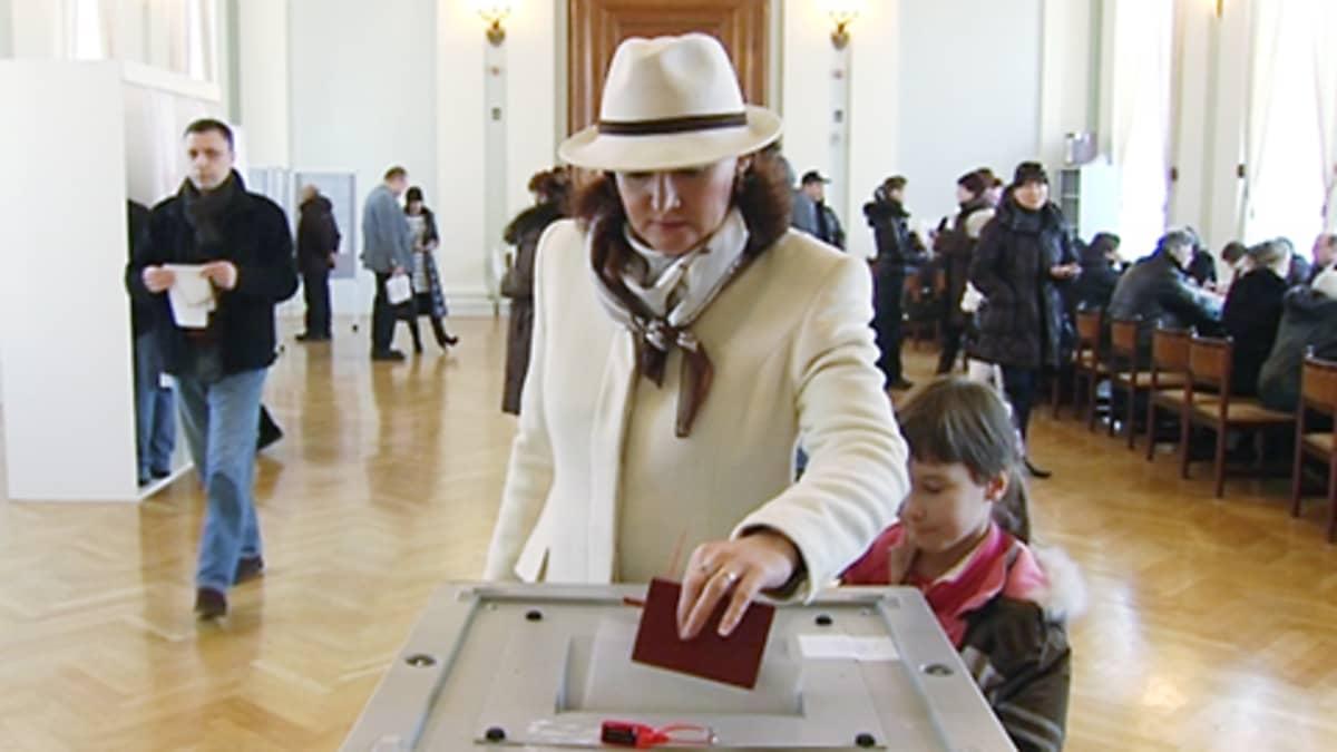 Nainen laittaa äänestyslippua uurnaan äänestyspaikalla.