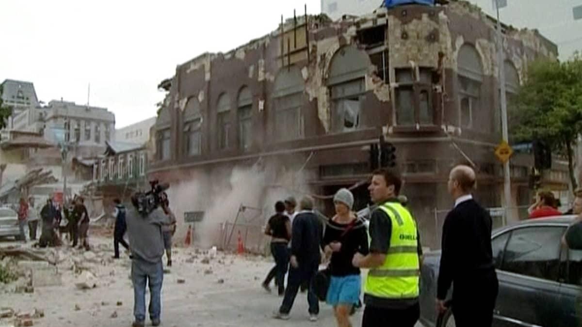 Pelastustyöntekijät ja sivulliset tarkastelevat järistyksen tuhoamaa rakennusta.