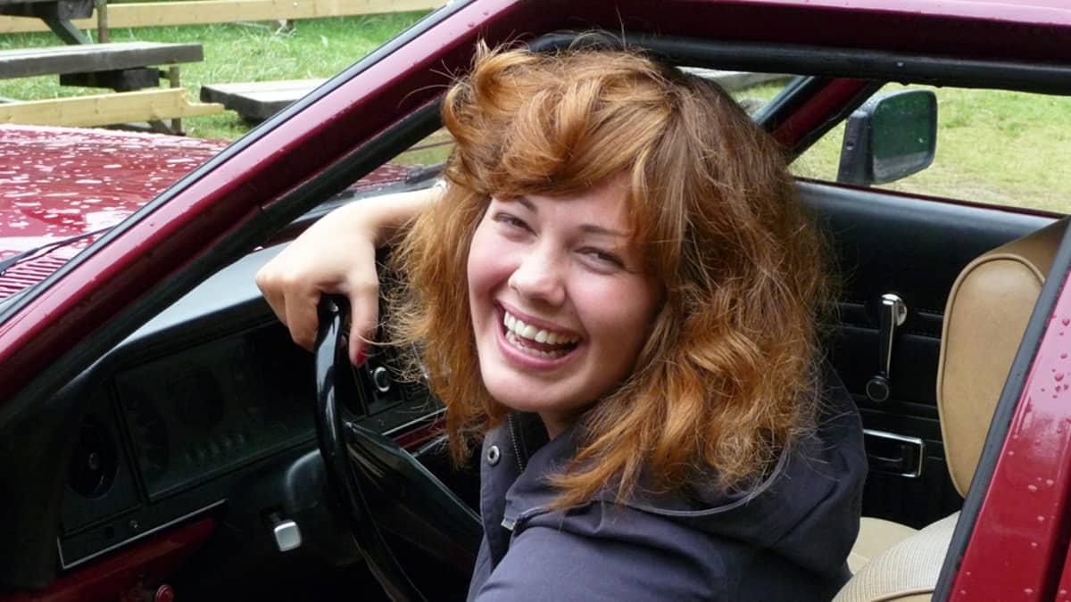 Autossa istuva nainen nauraa.