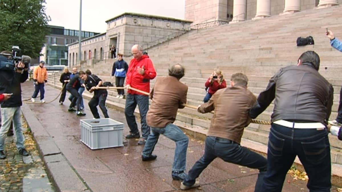 Kansanedustajia vetämässä köyttä eduskunnan edessä.