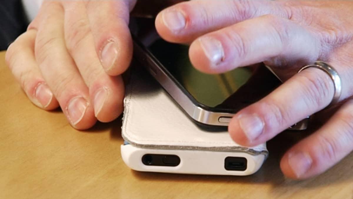 Kaksi älypuhelinta ja ihmisen kädet pöydällä.
