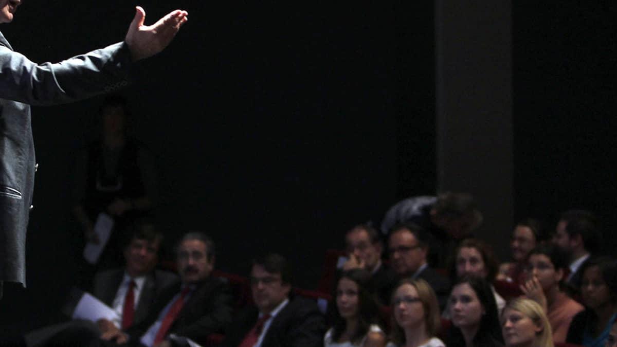 Johtaja puhuu lavalla yleisölle.