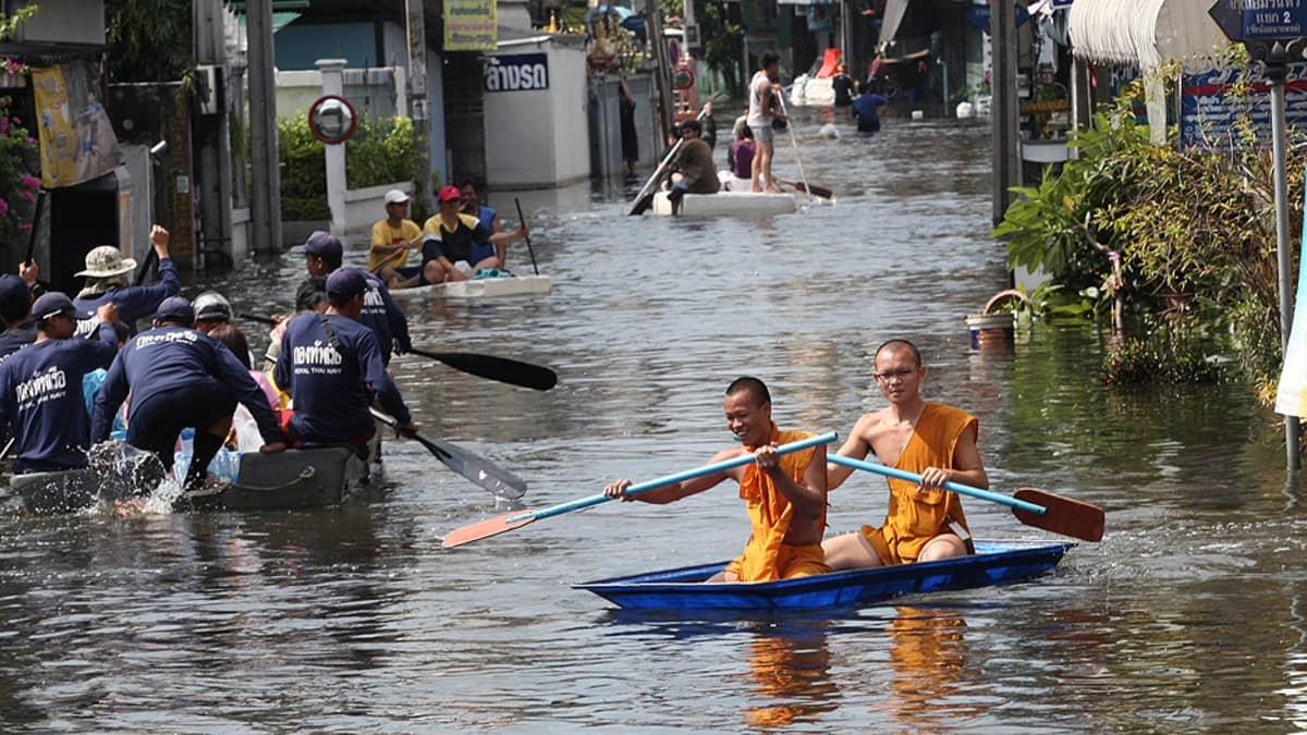 Kaksi buddhalaismunkkia meloi itsetehdyllä lautalla tulvivalla kadulla.