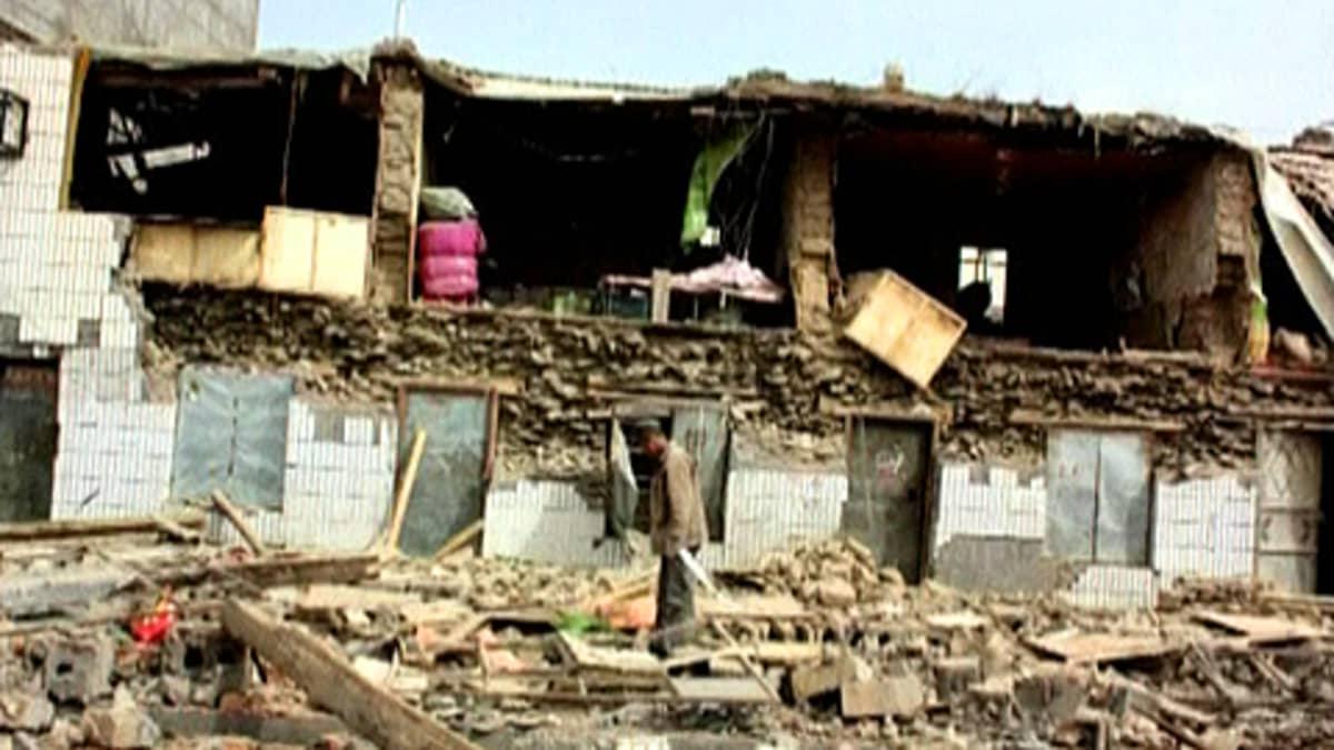 Kiinalaismies tutkii romahtaneen talon raunioita