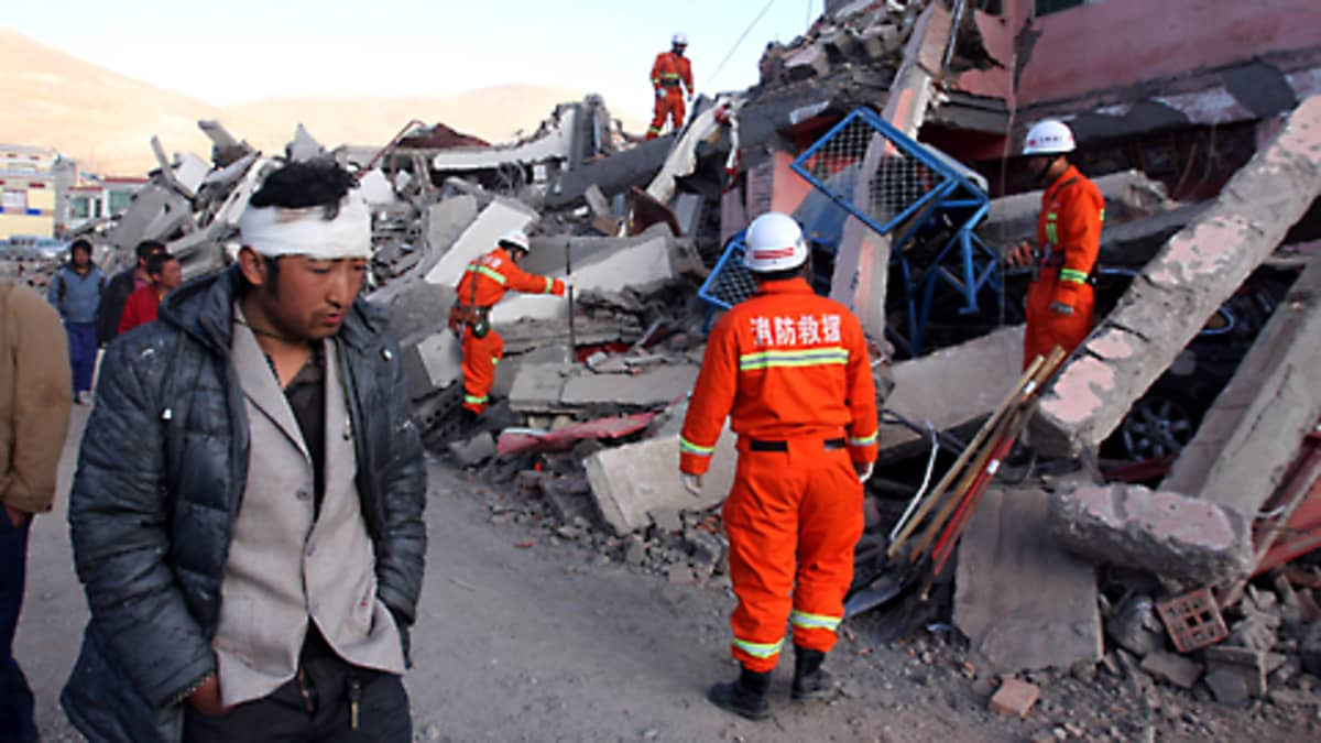 Loukkaantunut mies kävelee raunioita tutkivan pelastusmiehistön ohitse Jiegun kaupungissa