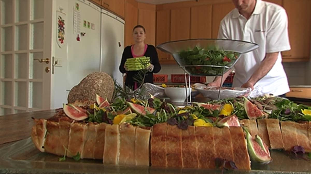 Pitopalvelun työntekijät asettelevat ruokaa keittiön pöydälle: leipää, melonia ja salaattia.