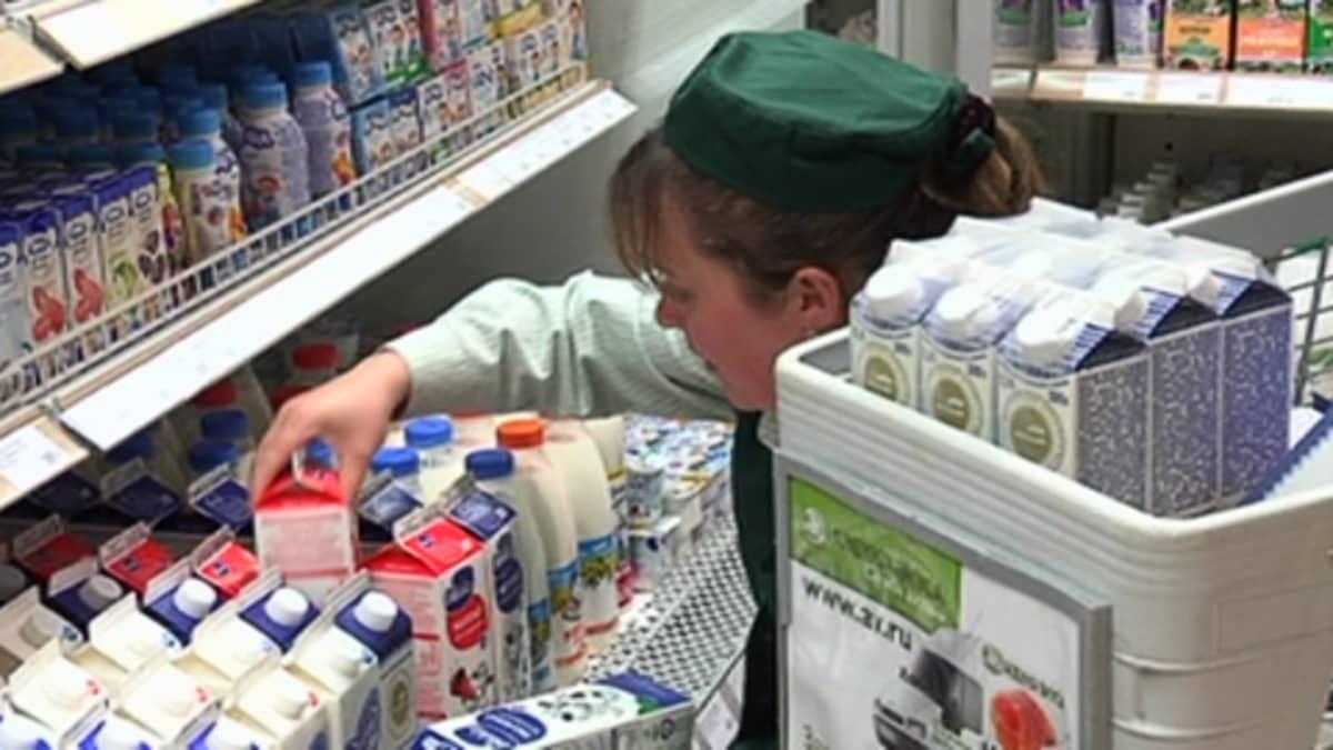 Myyjä asettelee maitopurkkeja myyntihyllyyn moskovalaisessa ruokakaupassa
