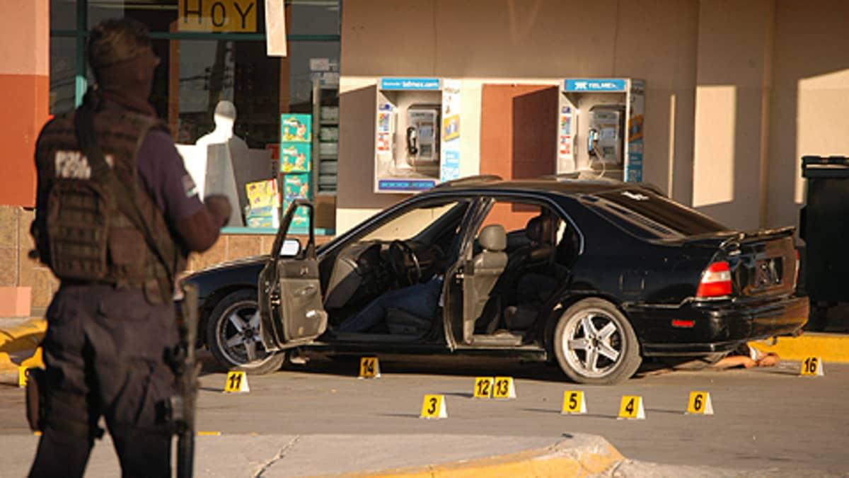 Raskaasti varustautunut poliisi henkilöauton edessä ammuskelun jälkeen. Maassa poliisin jättämiä numeroituja merkkejä.