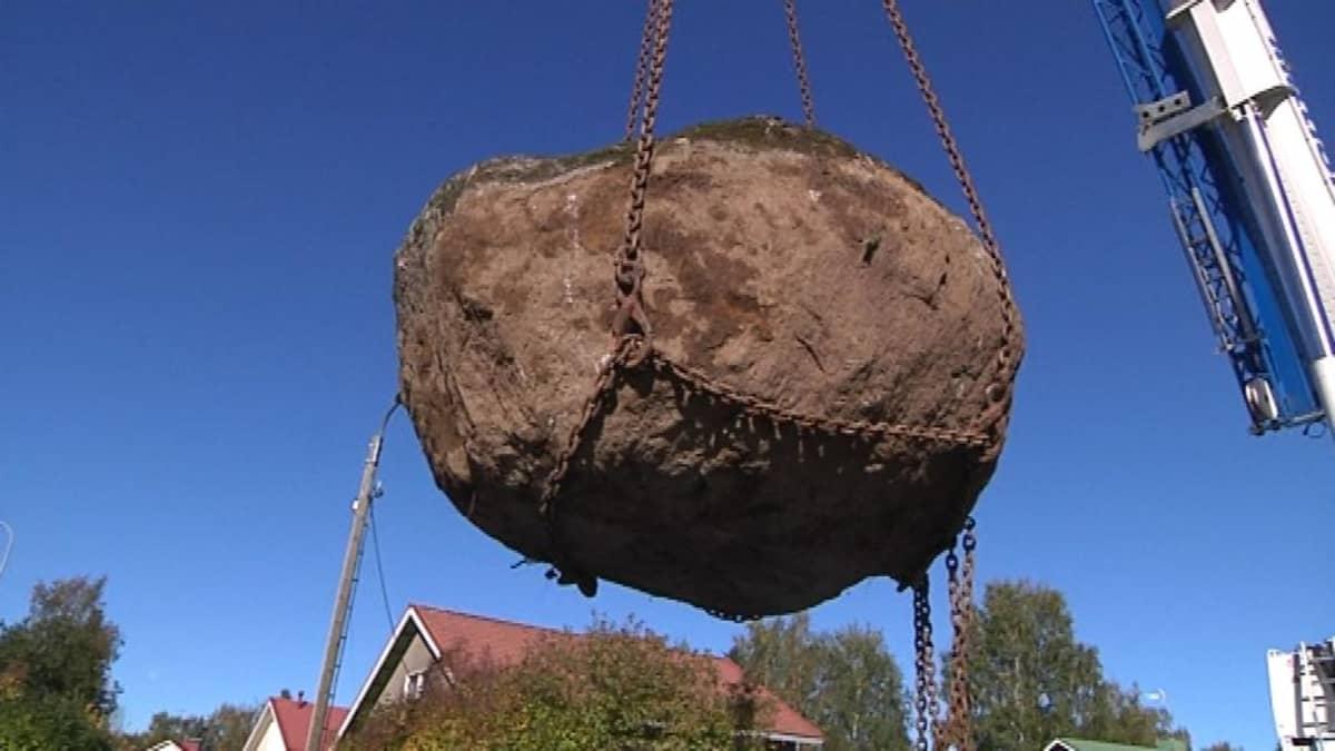 Suuri kivenjärkäle nosturin nostamana ilmassa
