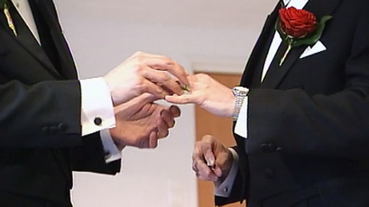 Miespari laittaa toisilleen sormuksia sormeen.
