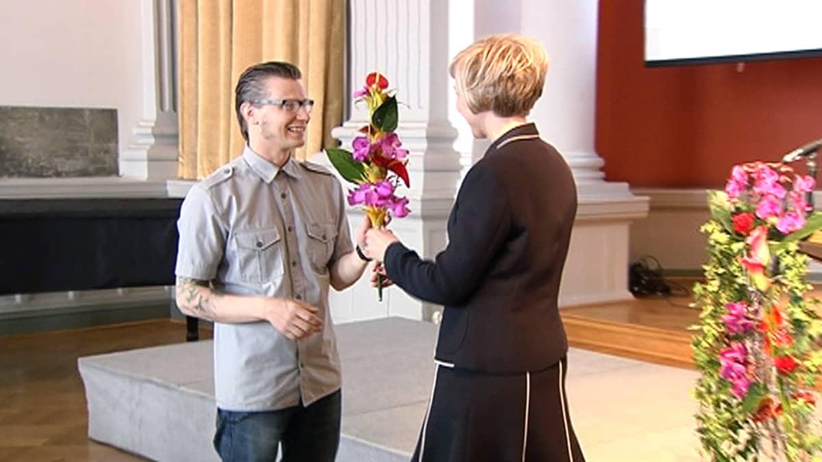 Nainen ojentaa miehelle kukkia.