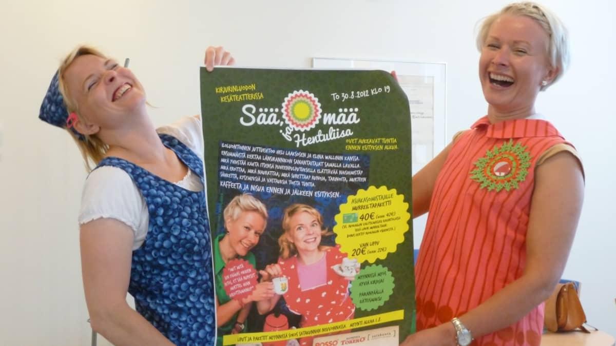 Heli Laaksonen ja Elina Wallin pitävät murre-ehtootaan mainostavaa julistetta.