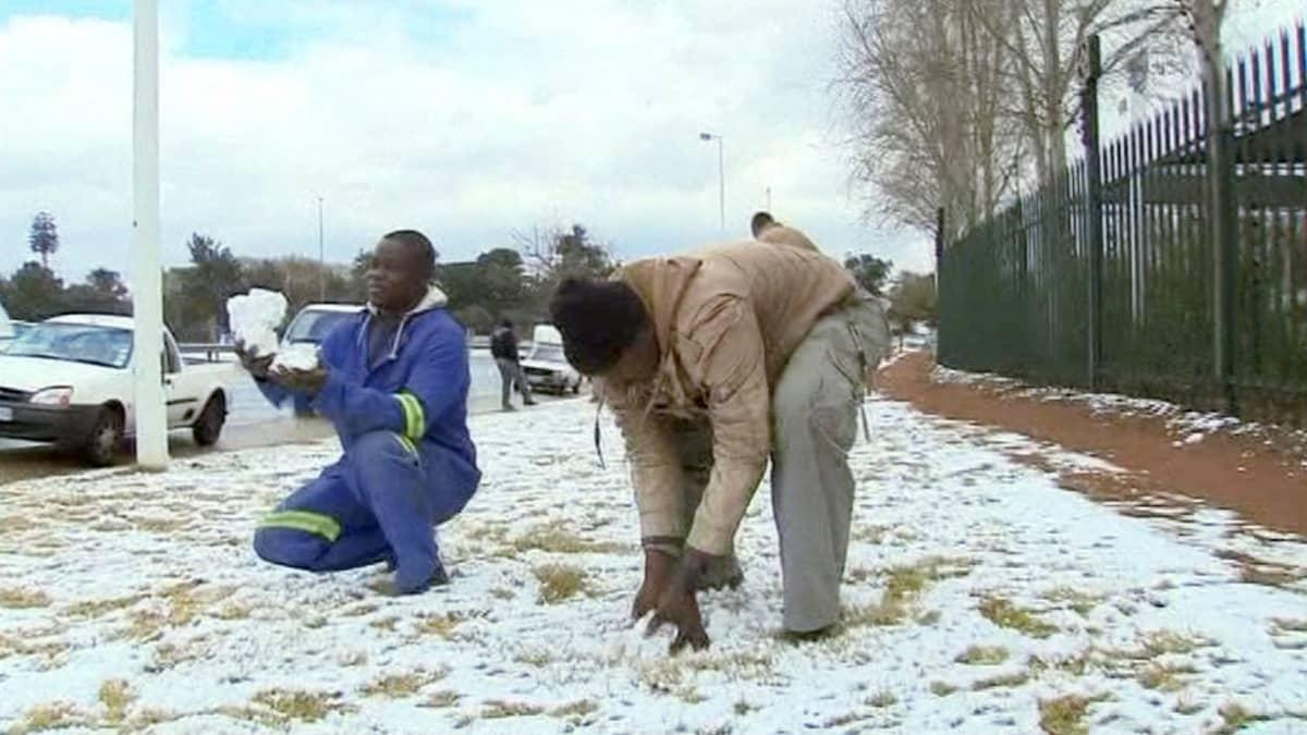 Miehet ihmettelevät Johannesburgissa satanutta lunta.