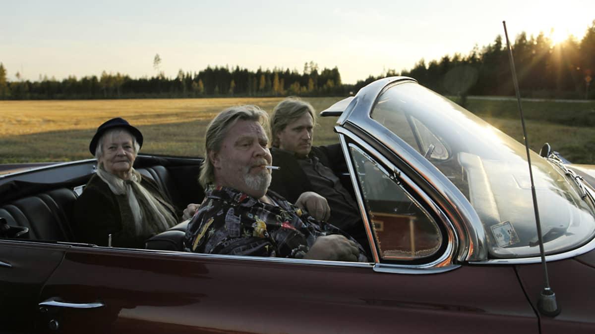 Vesa-Matti Loiri ja Samuli Edelmann istuvat avoauton etupenkillä. Mustaan huopahattuun ja huiviin sonnustautunut mummo istuu takapenkillä. Aurinko nousee taustalla.