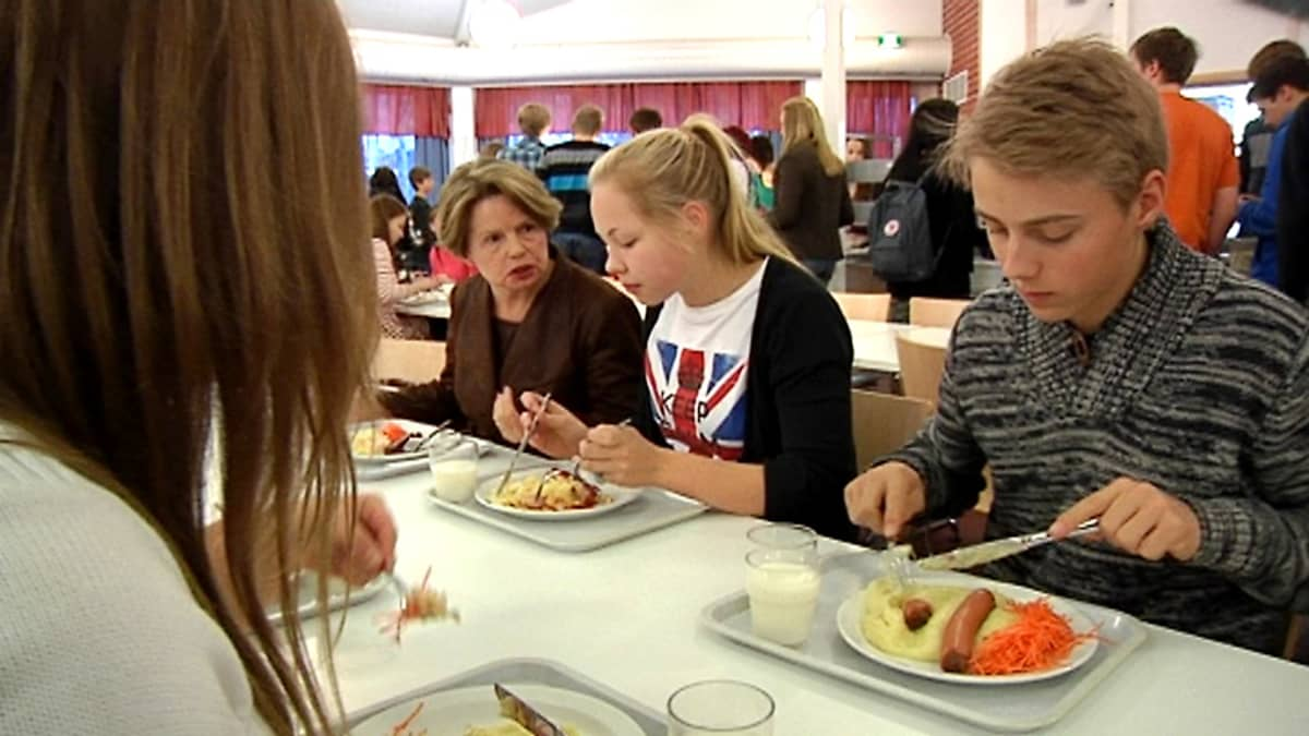 Ihmiset syövät kouluruokalassa uunimakkaraa.