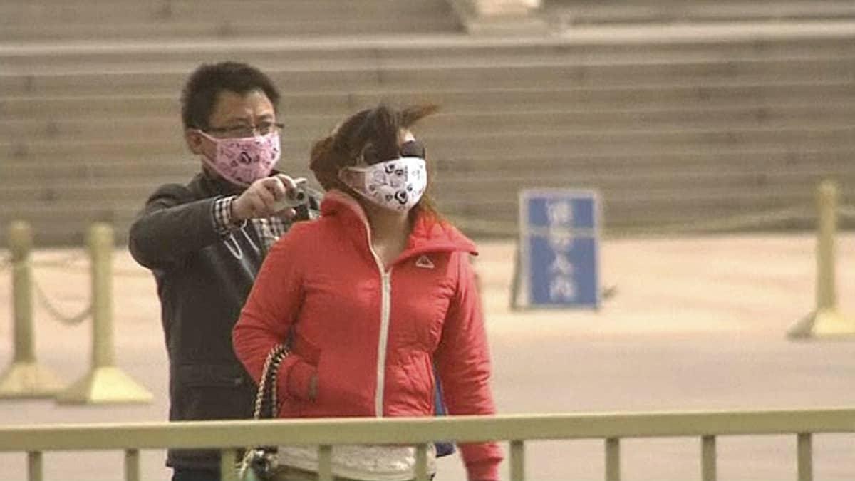 Ihmiset suojautuuvat hiekkamyrskyltä hengityssuojaimin ja aurinkolasein Pekingissä.