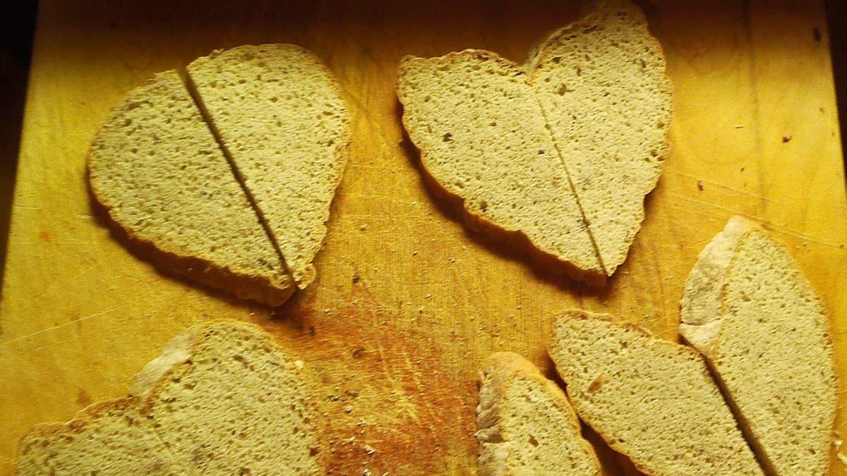 Sydämen muotoisia leipiä leikkuulaudalla.