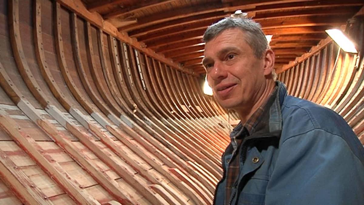 Kuvassa mies purjeveneen rakenteilla olevan rungon sisällä