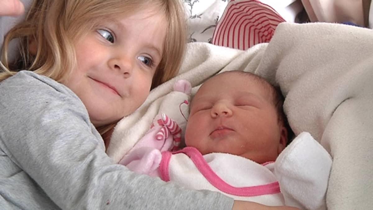 Kuvassa isosisko halaa vastasyntynyttä pikkusiskoa