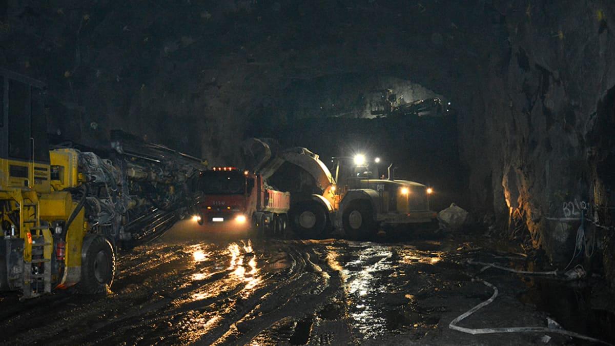 Kauhakuormaaja lastaa mursketta kuorma-autoon tunnelissa.