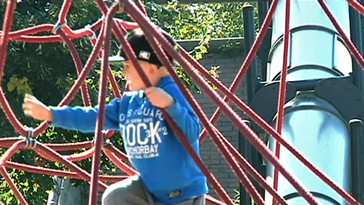 Nooa Nikkilä kiipeilee leikkipuistossa.