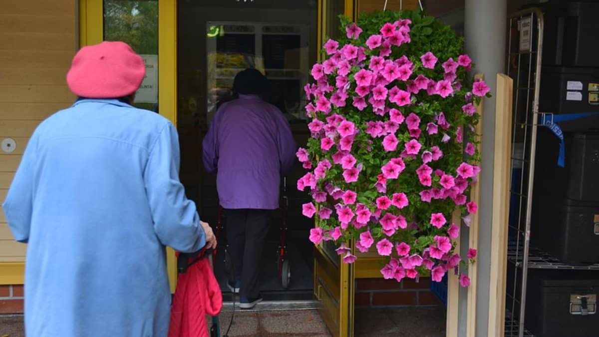 Kaksi vanhaa naista kävelee rollaattoreineen sisään hoivakodin ovesta.