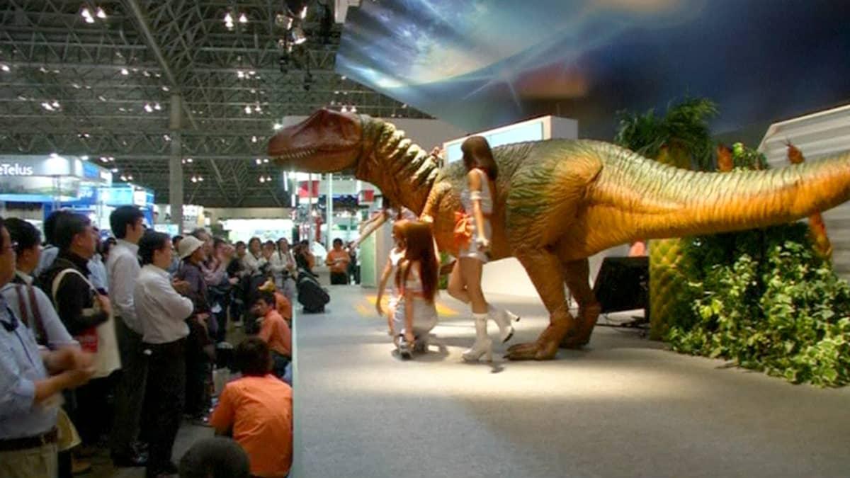 Kauko-ohjattava dinosaurusrobotti ja esiintyjiä teknologiamessuilla.