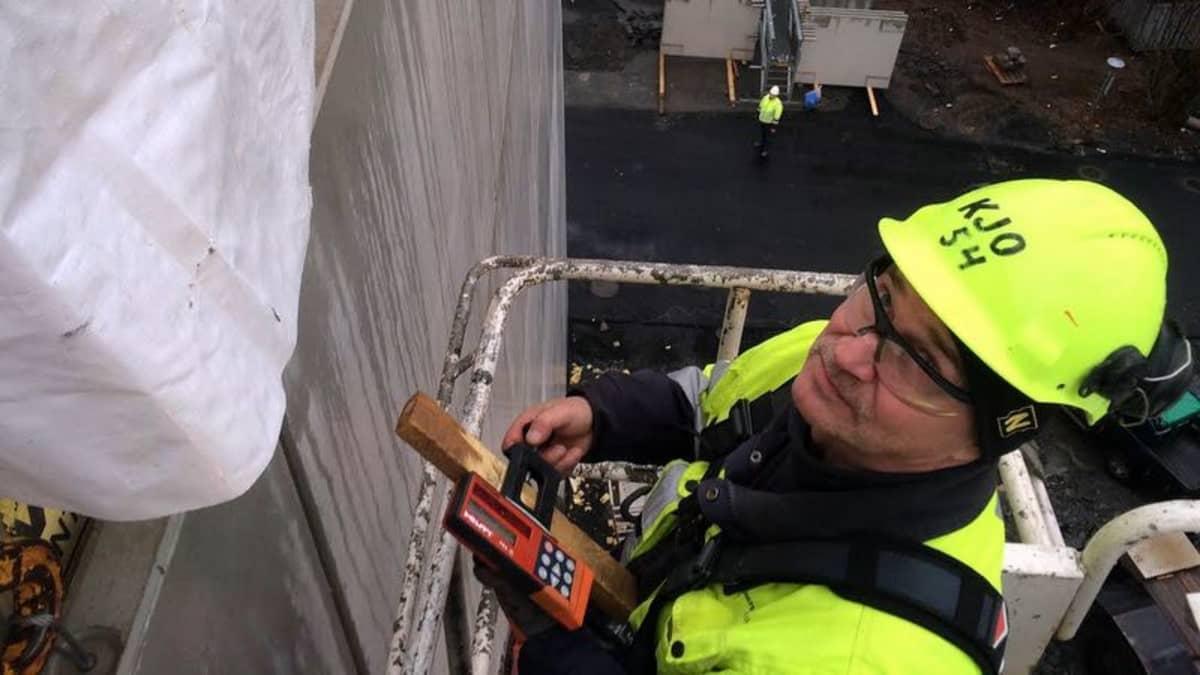 Rakennusmies työssä betoniseinän äärellä.