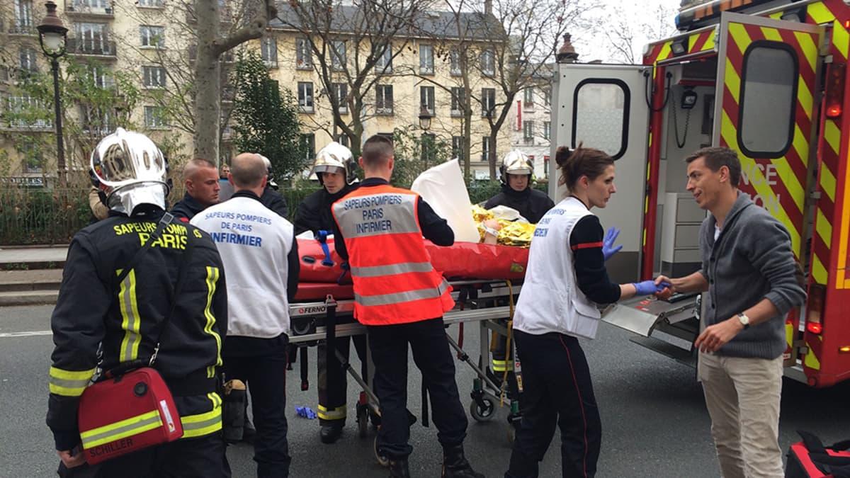 Palomiehet kantoivat uhria ambulanssiin keskiviikkona Pariisissa.