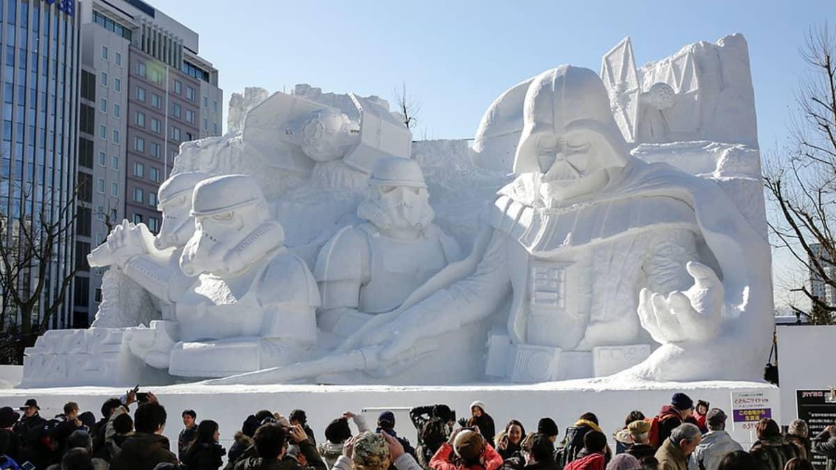 Ihmiset ottavat kuvia Tähtien sota -hahmoja esittävästä lumiveistoksesta Sapporon lumifestivaaleilla.