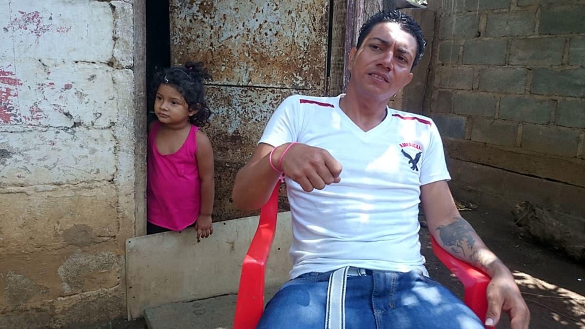 Marvin Morales istuu talonsa edessä. taustalla pieni tyttö