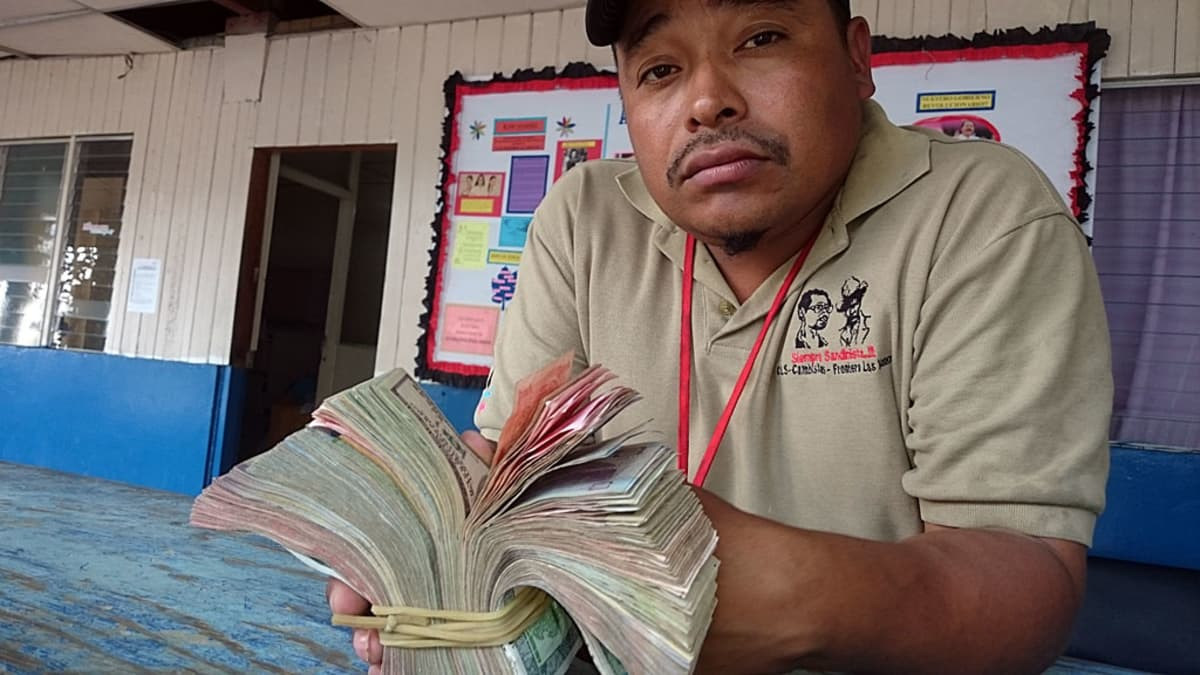 Rahanvaihtaja pitää kädessään suurta setelitukkua.