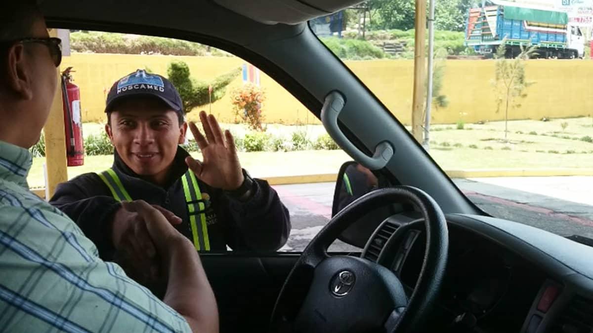 Mies tervehtii auton ikkunasta kuljettajaa.