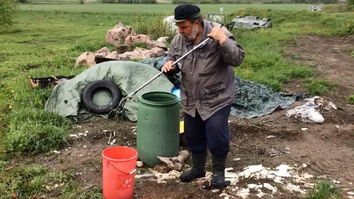 Luontoasiantuntija Urpo Koponen poistaa omakotitalotontilta kyykäärmeitä Pyhtäällä