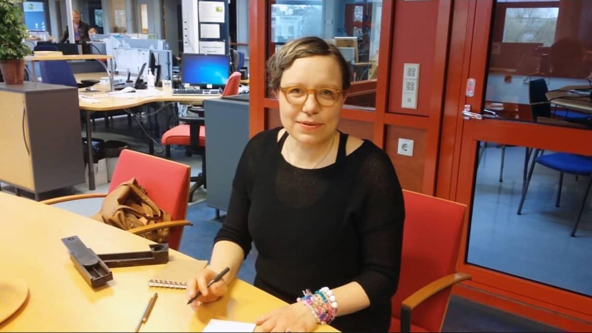 Kuvittaja Elina Warsta pöydän äärellä Yle Keski-Pohjanmaan toimituksessa Kokkolassa.