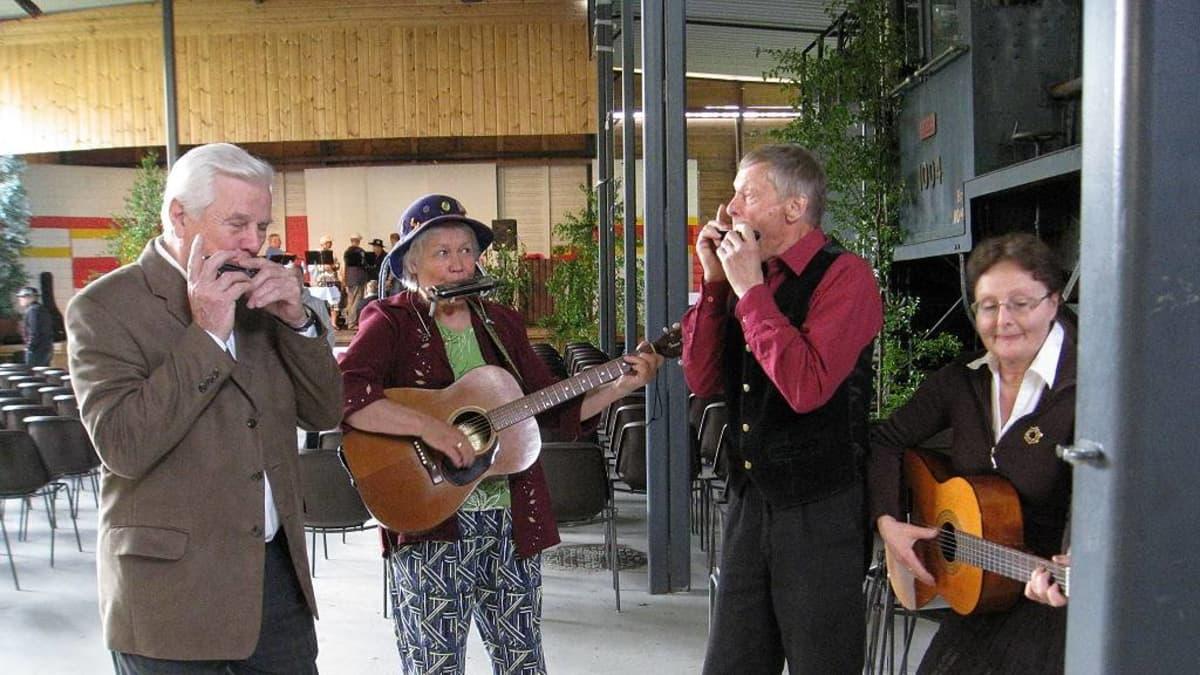 Neljä huuliharpun soittajaa areenan edessä.