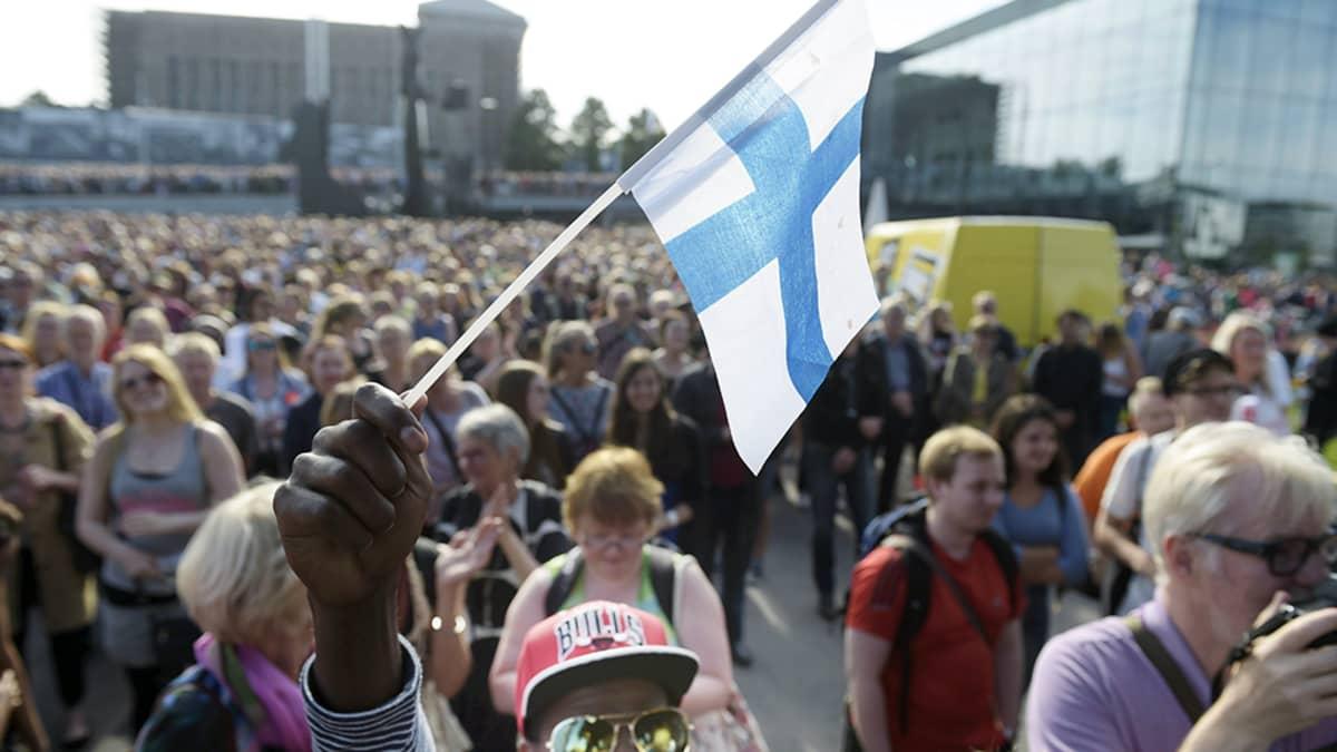 Mire Ibrahim heiluttaa Suomen lippua monikulttuurisuutta puolustavassa mielenosoituksessa Helsingin Kansalaistorilla.