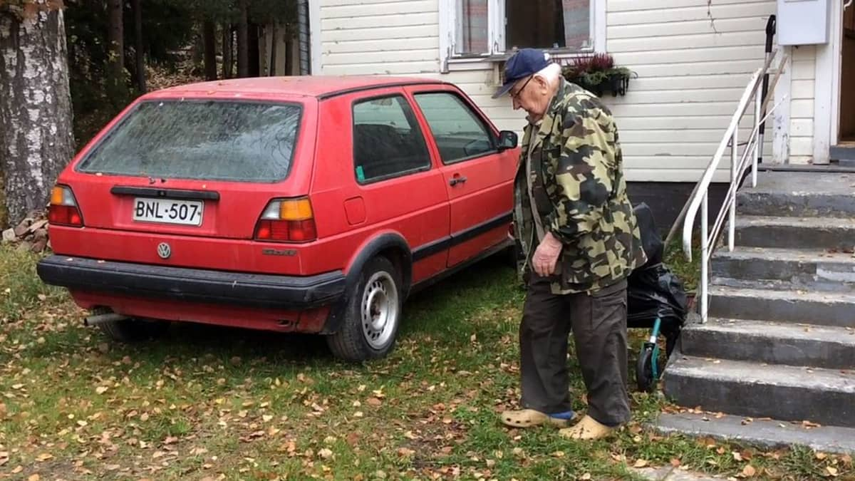 Maastopukuinen mies on menossa omakotitalon edessä odottavaan punaiseen autoon.