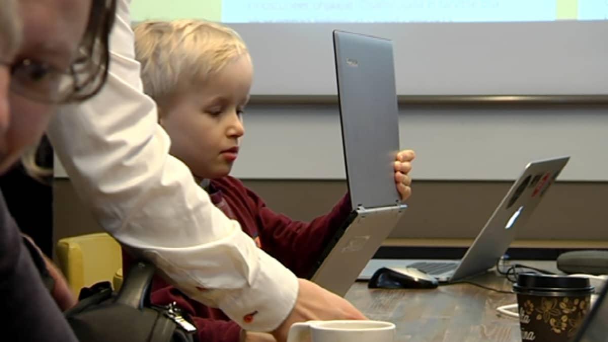 lapsi pitelee kannettavaa titokonetta