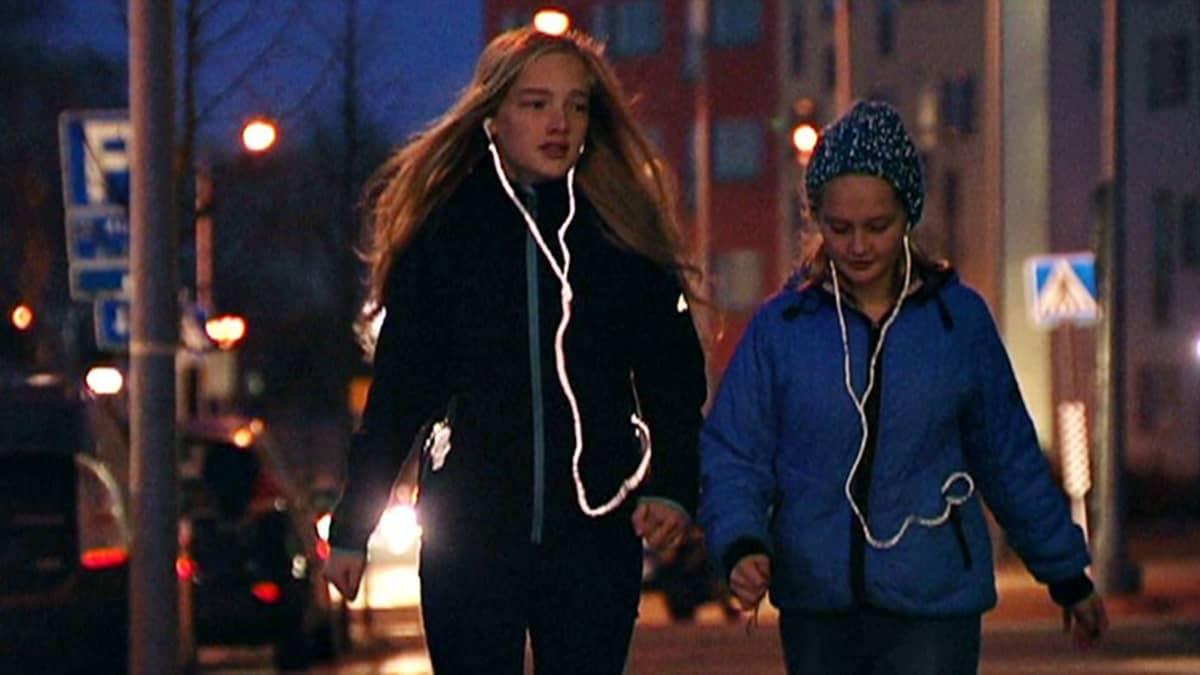Tyttöjä heijastavat kuulokejohdot päässä pimeällä kadulla.