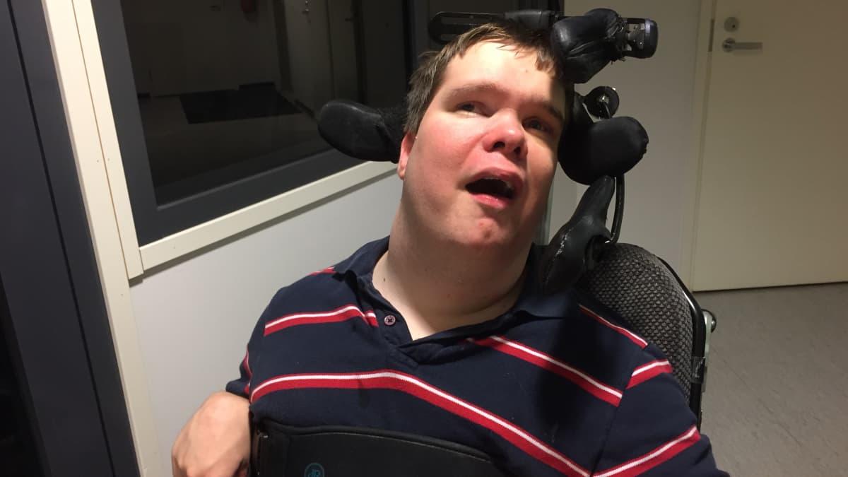 Mies istuu pyörätuolissa.