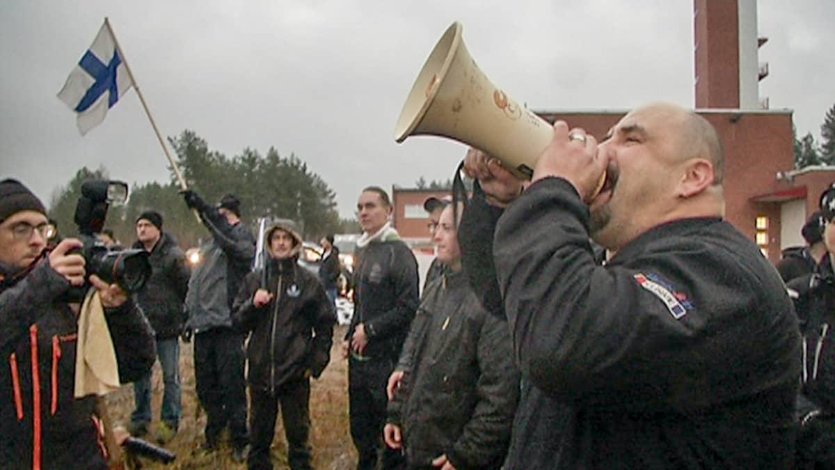 mies huutaa megafoniin, yksi heiluttaa suomenlippua