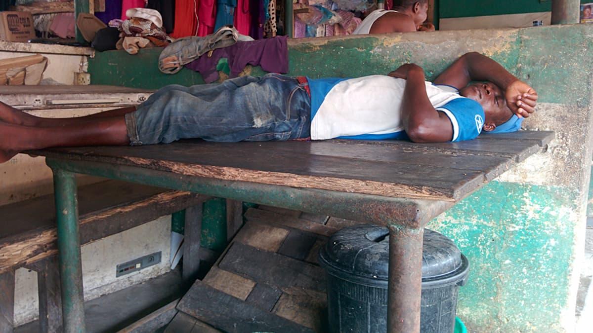 Mies makaa pöydällä.