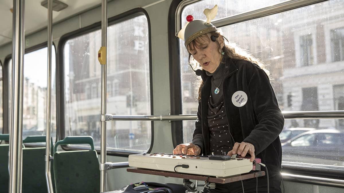 nainen soittaa kosketinsoitinta raitiovaunussa