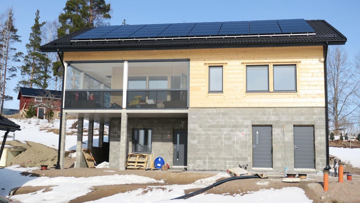 Rakennusvaiheessa oleva hirsitalo, jonka katolla on aurinkopaneeleita.